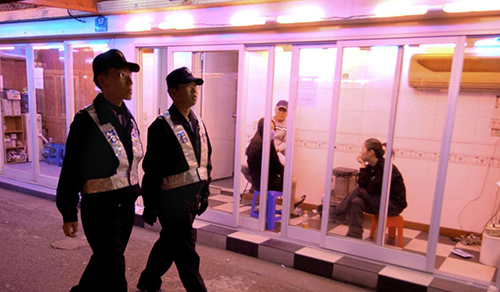 Cảnh sát Hàn Quốc đi qua phố đèn đỏ ởSeoul. Ảnh: AFP