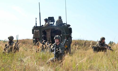 Lính Mỹ triển khai đội hình tam giác với sự yểm trợ của xe thiết giáp khi tuần tra. Ảnh: US Army.