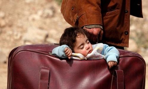 Em bé ngủ trong túi xách của bố khi hai người vội vã chạy khỏi Đông Ghouta. Ảnh: Reuters.