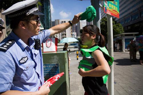 Một trường hợp người đi bộ ẩu bị phạt đội mũ xanh tại Thâm Quyến. Ảnh: CGTN.