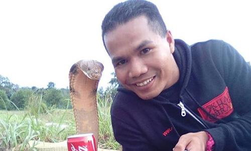 Abu Zarin Hussin chụp ảnh cùng một trong những con rắn của anh. Ảnh: BBC