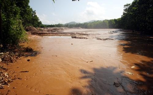 Hồ chứa chất thải khai thác vàng bị vỡ đã đổ xuống sông Quế Phương nước, bùn non khiến cá chết. Ảnh: Đắc Thành.
