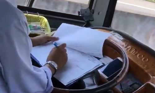 Tài xế vừa lái ôtô vừa ghi sổ sách