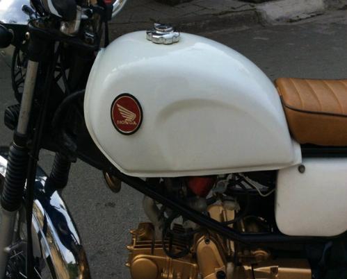 Yên xe được bọc lại thủ công, dáng nằm ngang có đệm mút, bình xăng và cốp gò được sơn trắng toàn bộ cùng điểm nhấn logo của Honda.
