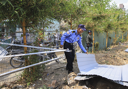 Bảo vệ tháo dỡ các tấm tôn bịt kín không gian biển của người dân Nam Ô, hôm 31/3. Ảnh: Nguyễn Đông.