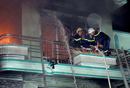 Cảnh sát cứu hỏa phun nước khống chế đám cháy. Ảnh: Thanh Châu.