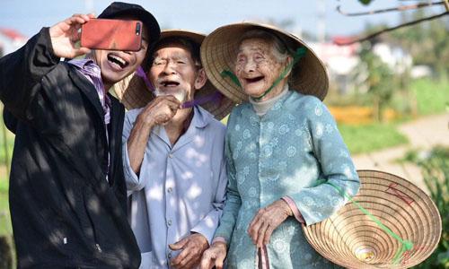 Cụ ông Le Van So, 94 tuổi (trái)và cụbà Nguyen Thi Loi, 88 tuổi chụp ảnh chung với du khách tại vườn rau của nhà, ở làng Trà Quế,xã Cẩm Hà, cách trung tâm phố phổ cổ Hội An3 km. Ảnh: Media Corp.