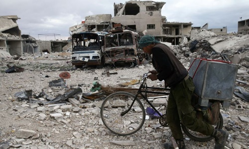 Người đàn ông dắt xe đạp đi giữa đống đổ nát tại thị trấn Douma, Đông Ghouta, ngoại ô thủ đô Damascus, Syria, ngày 30/3. Ảnh:Reuters.
