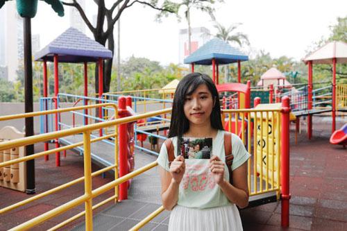 Trong tay cầm tấm ảnh thời thơ ấu, Chau Ho-oi đứng tại đúng công viên Kowloon nơi cô cùng mẹ tới vào năm 1999. Ảnh: Reuters.