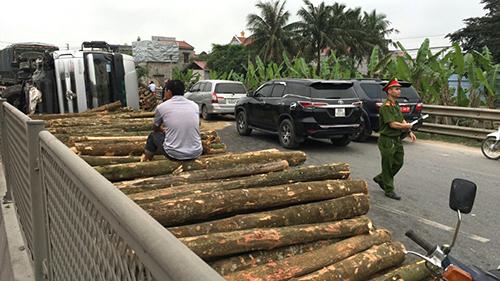 Hàng nghìn khúc gỗ đổ tràn ra đường sau khi xe tải lật. Ảnh: Lam Sơn.