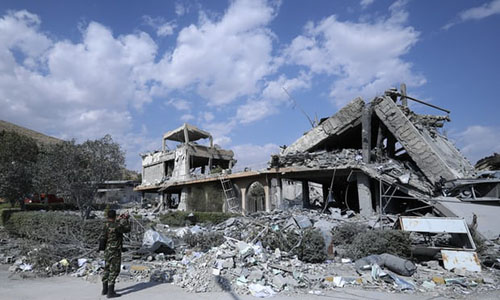 Một binh sĩ Syria quay lại cảnh đổ nát ở trung tâm nghiên cứu khoa học gần thủ đôDamascus sau vụ không kích của liên quân Mỹ, Anh và Pháp sáng ngày 14/4. Ảnh: AP.