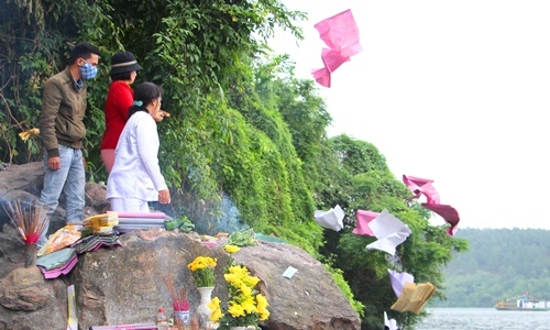 Người dân Huế ném vàng mã xuống sông Hương khi đi lễ hội