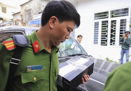Cảnh sát cầm ra một hộp dán kín băng dính.Ảnh: Nguyễn Đông