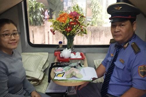 Nhân viên ngành đường sắt kiểm trachiếc ví để quên của nữ du khách quốc tế. Ảnh: NVCC
