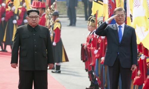 Lãnh đạo Triều Tiên Kim Jong-un và Tổng thống Hàn Moon Jae-in đi vào nhà Hòa Bình ởPanmunjeom ngày 27/4. Ảnh: AFP.