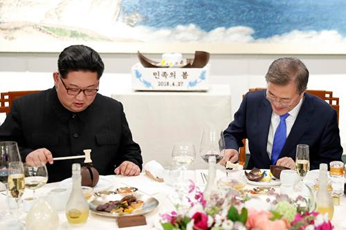 Ông Kim và ông Moon dùng búa nhỏ đập vỡ món bánhcó bản đồ bán đảo Triều Tiên trên bàn tiệc. Ảnh: AFP