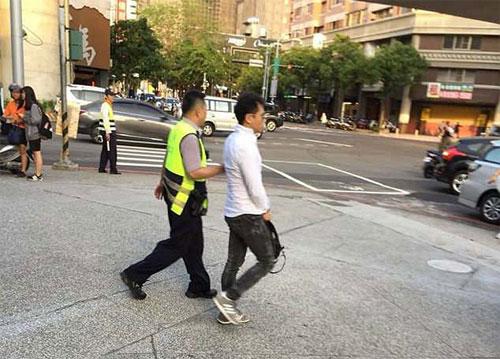 Chu bị cảnh sát đưa đi sau khi có hành động gây nguy hiểm cho người khác. Ảnh: Asiawire.