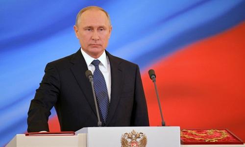 Ông Putin đặt tay lên Hiến pháp Nga, đọc lời tuyên thệ nhậm chức. Ảnh: Reuters.