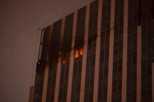 Lửa và khói bốc lên từ tầng 24 toà cao ốc trên đường Lê Văn Lương. Ảnh: MXH