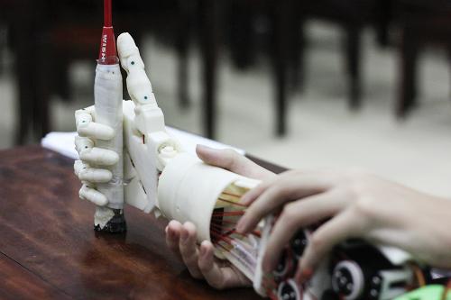 Với sự điều khiển bằng suy nghĩ, cánh tay robot của Huy và Khôi đã có thể cầm nắm các vật nhỏ. Ảnh: Dương Tâm