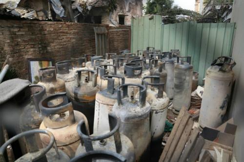 Nhiều bình gas công nghiệp bị cháy xém được đưa ra ngoài.Ảnh: Gia Chính