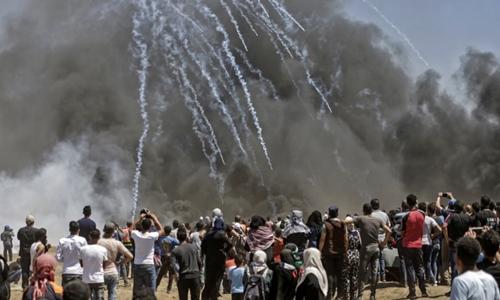 Người biểu tình Palestine đối mặt với hơi cay từ quân đội Israel tại ranh giới giữa Israel với Gaza ngày 14/5. Ảnh: AFP.