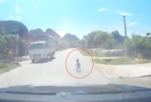 Hình ảnh cháu bé đang chập chững trên quốc lộ