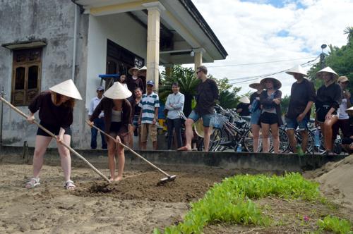 Du khách khám phá tour một ngày làm nông dân ở làng rau Trà Quế - TP Hội An. Ảnh: Đắc Thành.
