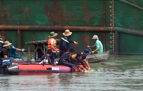 Cảnh sát cứu hộ vớt thi thể bé trai ngay vị trí sà lan chìm. Ảnh: Nguyệt Triều.