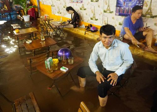Nước tràn vào quán cà phê sau trận mưa tối qua. Ảnh: Quỳnh Trần.