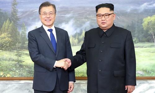 Tổng thống Hàn Quốc Moon Jae-in (trái) bắt tay lãnh đạo Triều Tiên trong cuộc gặp hôm nay ở DMZ. Ảnh: Yonhap.