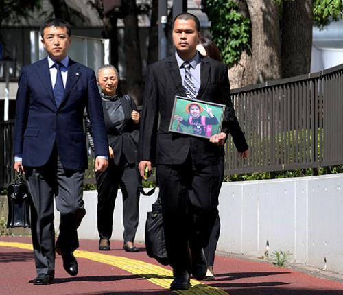 Anh Lê Anh Hào cầm di ảnh con gái đến phiên tòa. Ảnh: Asahi.
