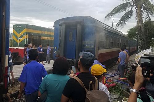 Người dân và hành khách theo dõi việc dập lửa. Ảnh: Nguyễn Đông.