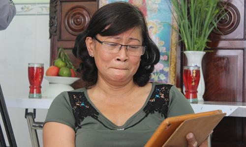Bà Bông xúc động bên kỷ vật là chiếc máy tính bảng của con trai tặng. Ảnh: An Long.