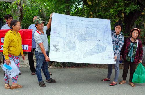 Người dân Thủ Thiêm căng bản đồ quy hoạch và biểu ngữ phía trước trụ sở Trung tâm bồi dưỡng chính trị quận 2. Ảnh: Thành Nguyễn
