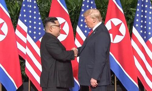 Kim Jong-un (trái) và Donald Trump lần đầu tiên bắt tay khi gặp mặt ở Singapore. Ảnh: AP.
