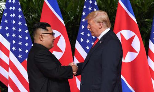 Tổng thống Mỹ Donald Trump và lãnh đạo Triều Tiên Kim Jong-un hôm nay bắt tay tại cuộc gặp đầu tiên ở Singapore. Ảnh: Straits Times.