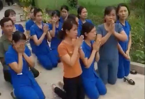 Các giáo viên và bảo vệ quỳ tại trường. Ảnh cắt từ video