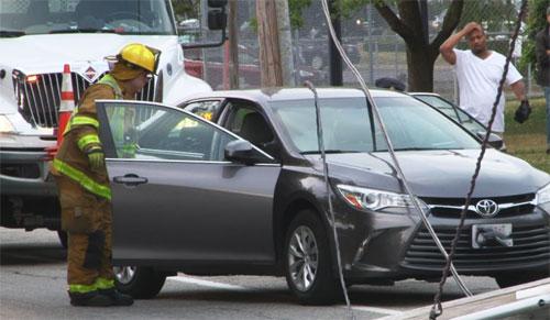 Chiếc sedan hiệu Toyota bị dây điện rơi trúng và cả 3 người trên xe, trong đó có hai đứa trẻ, bị mắt kẹt. Ảnh: NBC 10 News.