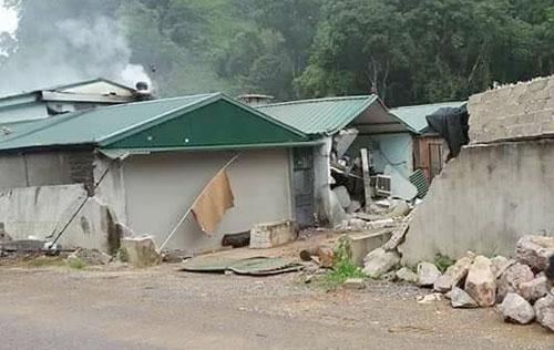 Bức tường vây và nhà cấp bốn lợp mái tôn bị phá hủy. Ảnh.Việt Quân