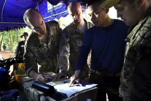 Quân nhân Thái và Mỹ bàn thảo kế hoạch bên ngoài hang động ngày 28/6. Ảnh: AFP.