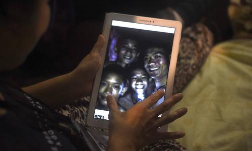 Bức ảnh những cậu bé tươi cười khi được cứu được gia đình họ truyền tay nhau. Ảnh: AFP.