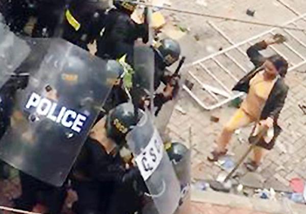 Cảnh sát bị ném đá khi cố ngăn dòng người gây rối. Ảnh cắt từ clip.