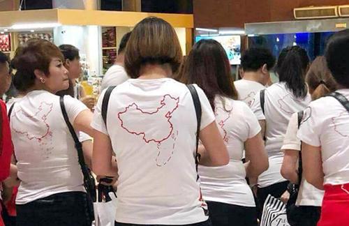 Nhóm khách Trung Quốc mặc áo in hình đường lưỡi bò nhập cảnh sân bay Cam Ranh, hồi tháng 5, do công ty này đưa sang Việt Nam du lịch. Ảnh: Vũ Chả.
