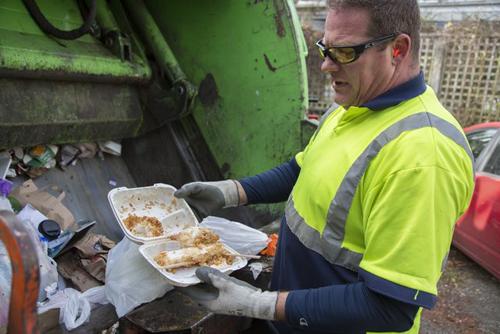 Nhân viên vệ sinh phát hiện thức ăn thừa trong thùng rác. Ảnh: Steve Ringman.