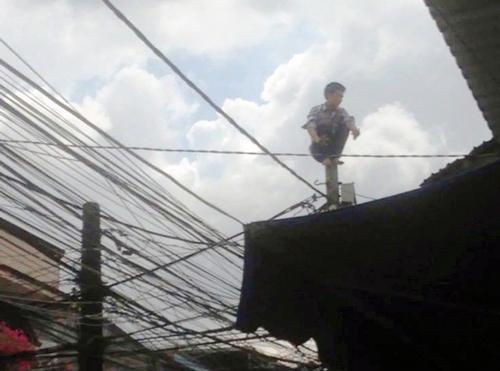 Anh ta ngồi trên đỉnh trụ điện. Ảnh: Tin Tin
