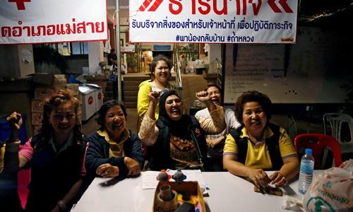 Các tình nguyện viên cười vui khi nghe tin toàn bộ thành viên đội bóng nhí Thái Lan đã được giải cứu. Ảnh: Reuters.