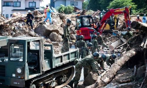 Lực lượng cứu hộ và binh sĩ dọn dẹp đống đổ nát trên một con phố sau trận lụt ở Kumano, tỉnh Hiroshima, ngày 9/7. Ảnh: AFP.