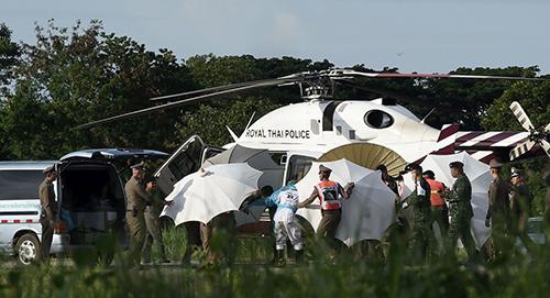 Cứu hộ di chuyển một cậu bé lên trực thăng hôm qua. Ảnh: AFP
