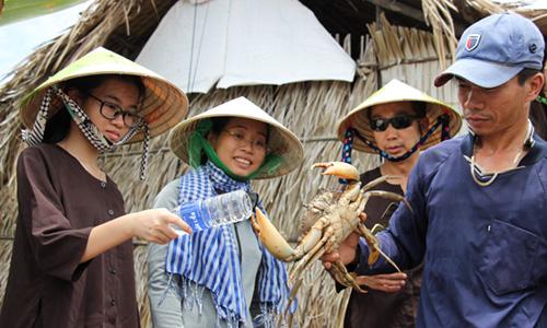Ngọc Hiện (choàng khăn) giới thiệu cua biển tự nhiên với du khách. Ảnh: Hoàng Nam